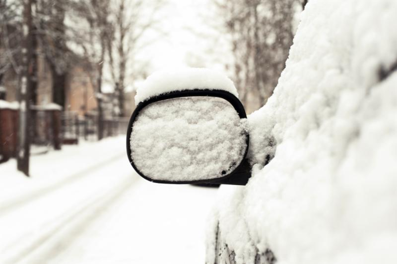 Car on a snowy street with windows and side mirror covered with snow